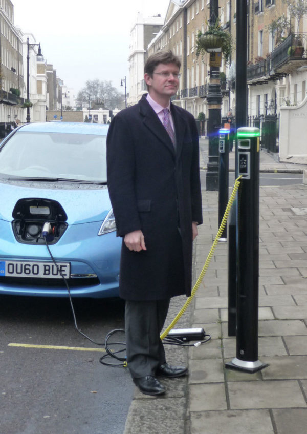 Member of UK government standing by an electric vehicle charging