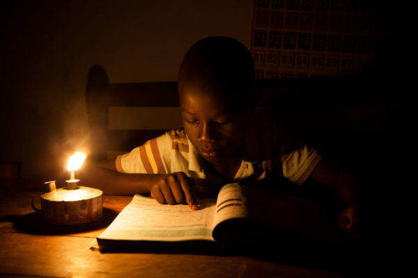 A young boy uses a tin kerosine lantern to study in Migori, Kenya. Image: SolarAid Photos, Creative Commons licence